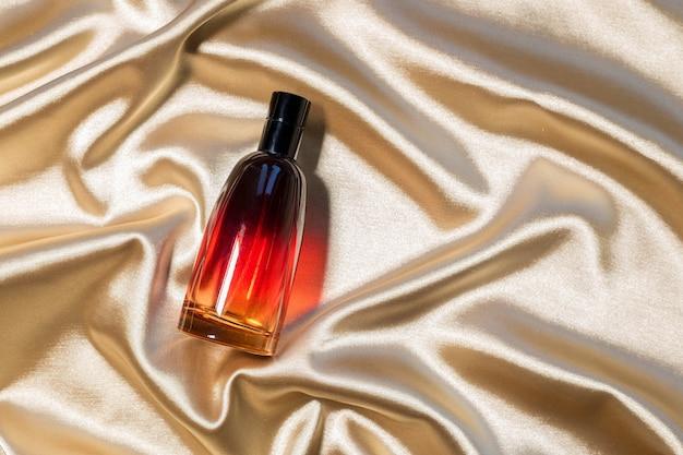 . 골드 접힌 실크 직물 배경에 향수 병. luxery 향기 향수 화장품 미용 제품.