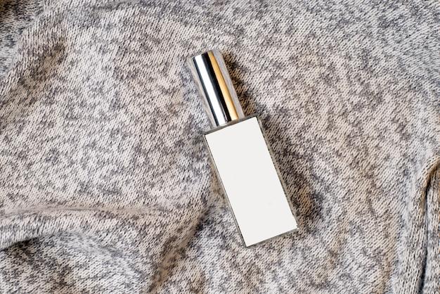 灰色のしわくちゃの生地の香水瓶。美容、スキンケア。