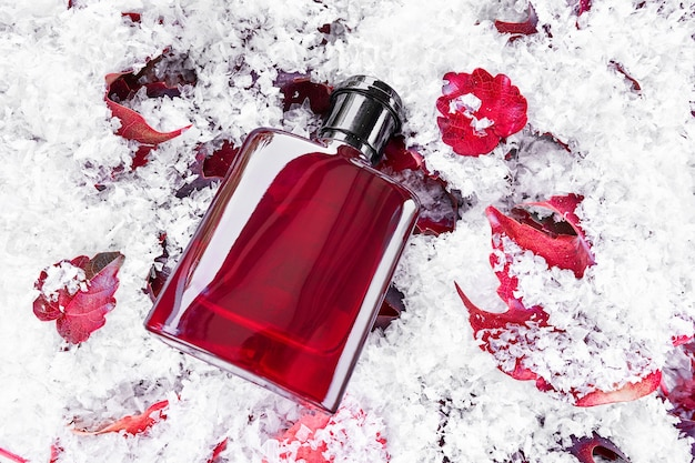 눈 배경으로 덮여 붉은 잎에 향수 병. 포장 디자인 모형. 브랜딩 아이덴티티