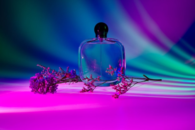 Perfume bottle and pink flower in pink, green, and blue color studio light.