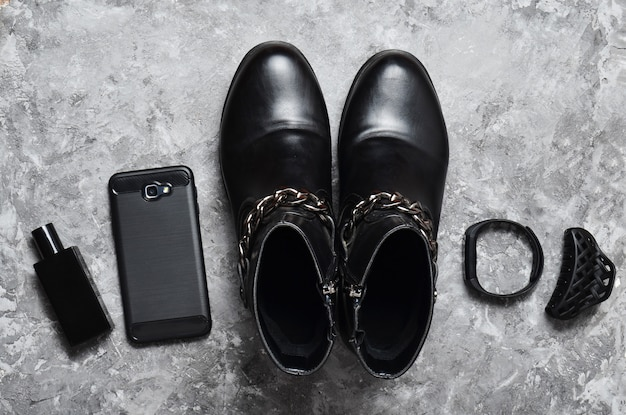 Флакон духов, кошелек, ручка, смартфон, умный браслет, солнцезащитные очки. женские сапоги, аксессуары, гаджеты для макета бизнес-леди на бетонной поверхности. черный серый цвета тенденция плоской планировки. вид сверху.