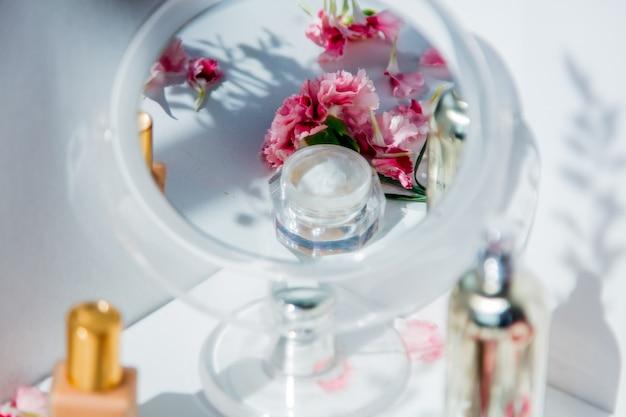 白い壁の周りに香水瓶、スキンケアクリーム、ナデシコの花