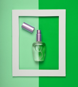 A perfume bottle in a white frame on a colored pastel.