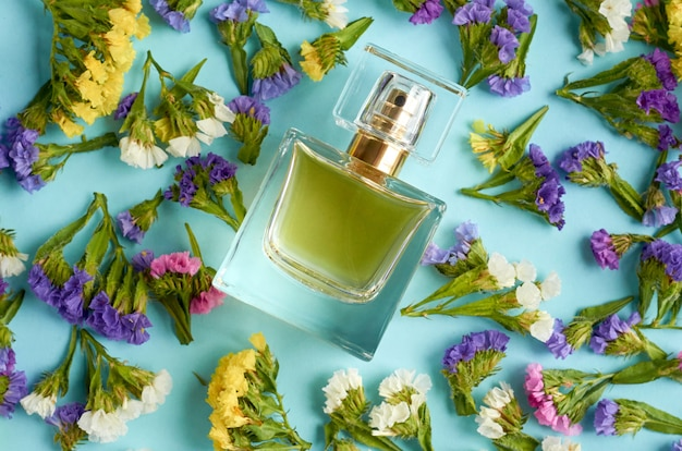 Perfume bottle with colored flowers on blue surface.
