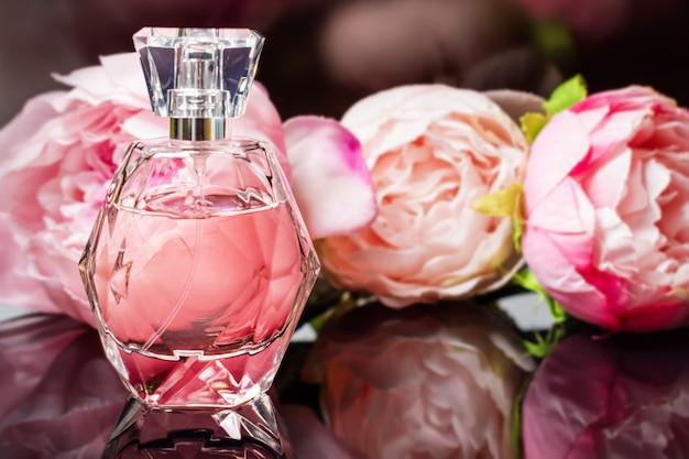 暗い表面に花が付いている香水瓶