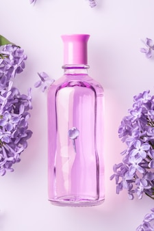 Perfume bottle with lilac flowers on white wall