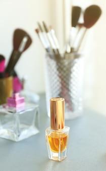 Флакон духов с инструментами для макияжа и косметикой на столе