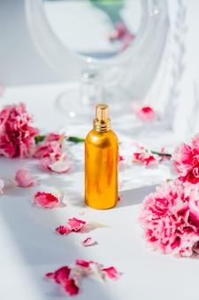 白い壁の周りに鏡とナデシコの花が付いている香水瓶
