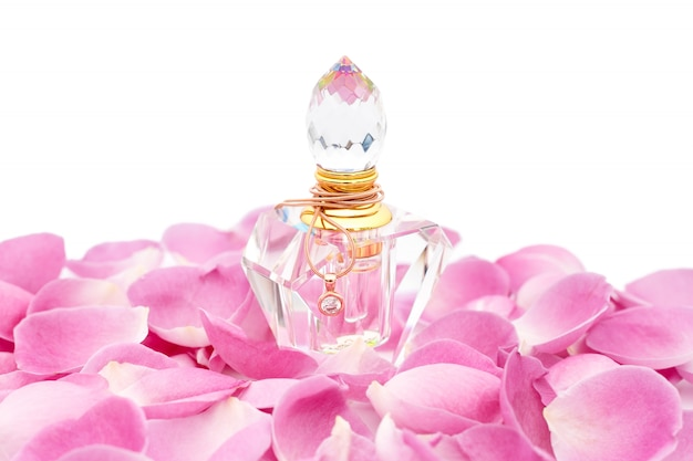 Perfume bottle with necklace among flower petals. perfumery, cosmetics, fragrance collection