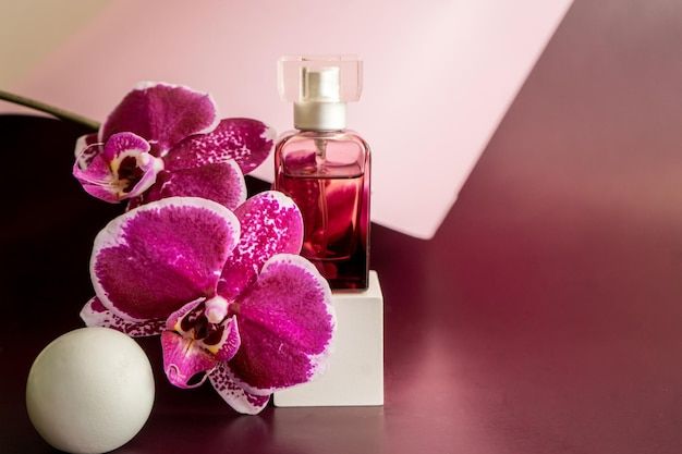 Perfume bottle with orhid flowers. perfumery cosmetics toilet water fragrance collection. high quality photo