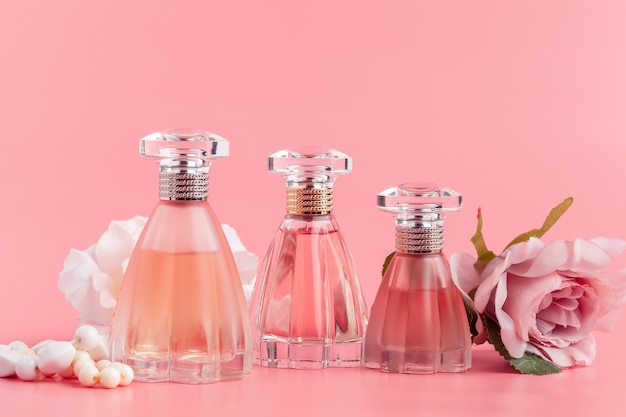 Perfume bottle with roses on pink fabric