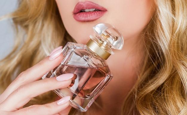 향수병 여자 스프레이 아로마. 향수 병을 들고 여자입니다. 향수 병을 가진 여자입니다. 향수를 사용하는 아름다운 소녀. 향수 병을 가진 여자입니다. 여자는 향수 향수를 선물합니다.