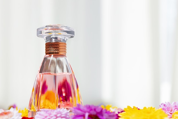 Perfume bottle for women in flower buds close up