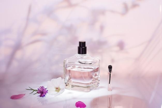 ピンクの花の背景に植物と香水瓶とサンプラー