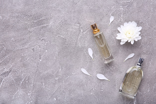 Perfume bottles with flowers on grey concrete