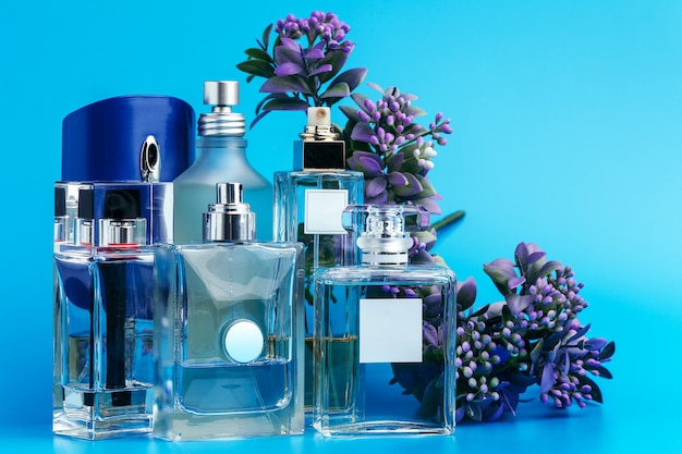 Perfume bottles with flowers on a light blue