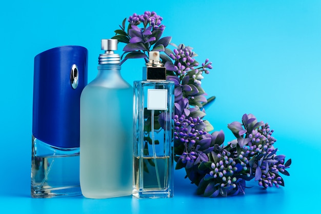 Perfume bottles with flowers on light blue