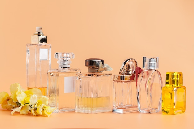 Perfume bottles with flowers petals on beige