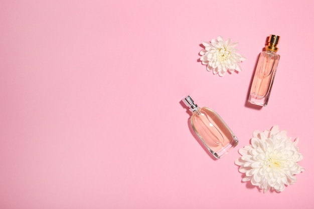 Perfume bottles with flowers on pink