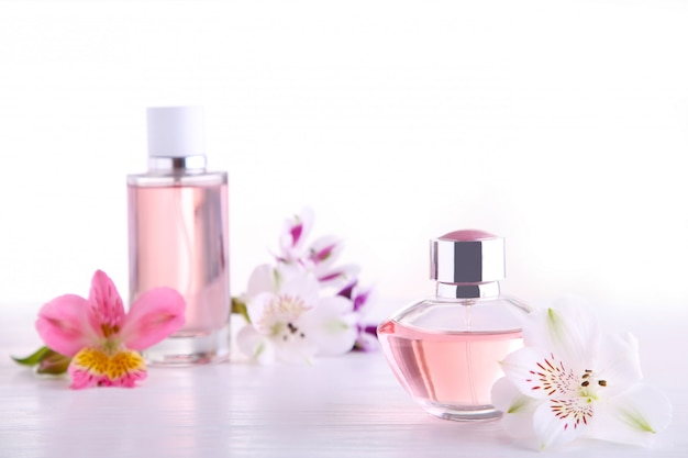 Perfume bottles with flowers on white