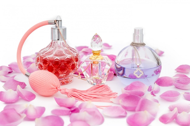 Perfume bottles with necklaces among flower petals. perfumery, cosmetics, fragrance collection