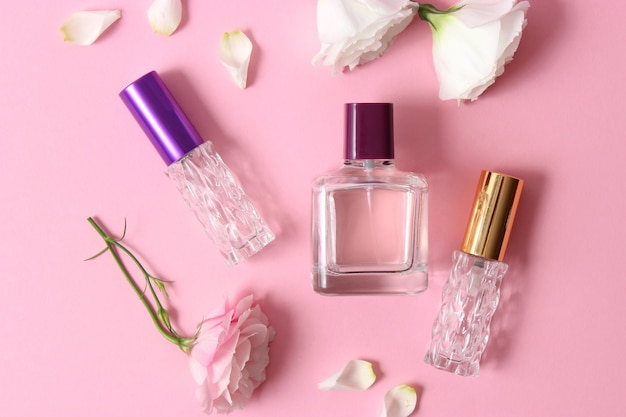 Perfume and flowers on a colored background
