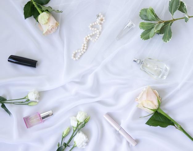 Духи, цветы, украшения, жемчуг, косметика на белом шифоновом фоне. женственная элегантная концепция моды. плоская планировка.