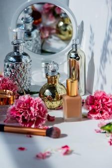 香水、ファンデーションクリーム、ブラシ、白い壁にナデシコの花をあしらった反射。メイクのコンセプト