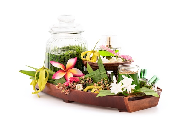 Perfume from fragrant flowers such as ylang-ylang flower, rose, jasmine and pandanus green leaves isolated.