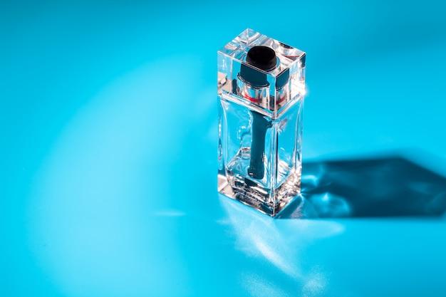 Perfume glass bottle on light blue background. eau de toilette