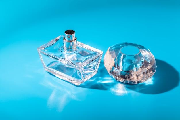 Perfume glass bottle on light blue. eau de toilette