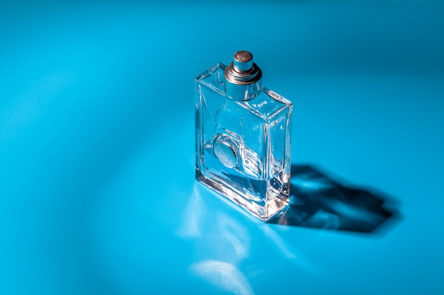 Perfume glass bottle on light blue. eau de toilette