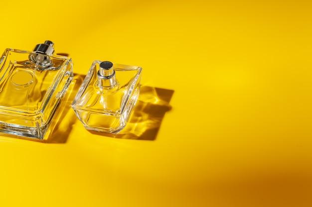 Perfume glass bottle on light yellow . eau de toilette