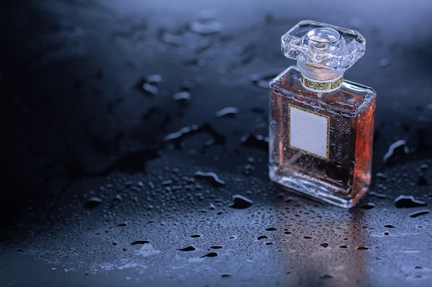 Perfume on gray wet background