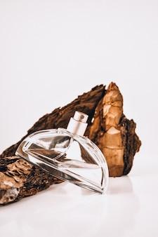 Духи в коре дерева с каплями воды. текстура. понятие свежести и естественности. аромат дерева и утренней росы. осенняя меланхолия. копировать пространство, масло смешивается с водой в пульверизаторе.