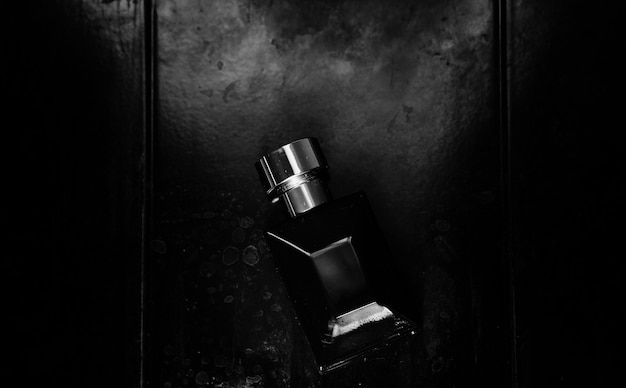 Perfume for men. black glass bottle on dark metallic background.