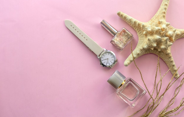 Perfume, nail, polish watch on table.