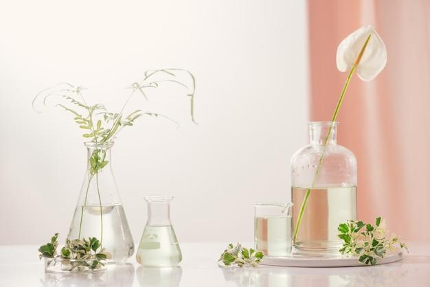 Концепция парфюмерных масел. лабораторная посуда с настоянной цветочной водой на столе
