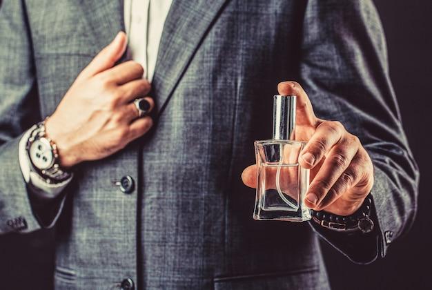 香水またはケルンのボトルと香水、化粧品、香りのケルンのボトル、ケルンを保持している男性。ビジネススーツを着た腕時計を手に取ってください。