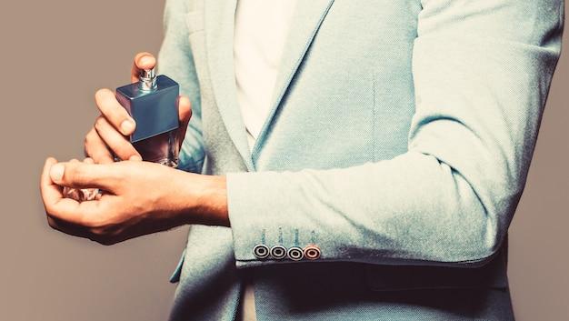 香水またはケルンのボトル。男性の香りと香水、化粧品。男の香水、香り。男性的な香水。香水のボトルを持っている男。ファッションケルンボトル。