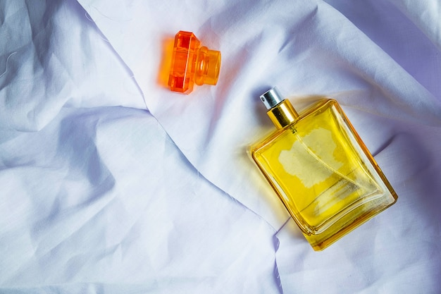Perfume and perfume bottles on a white cloth floor