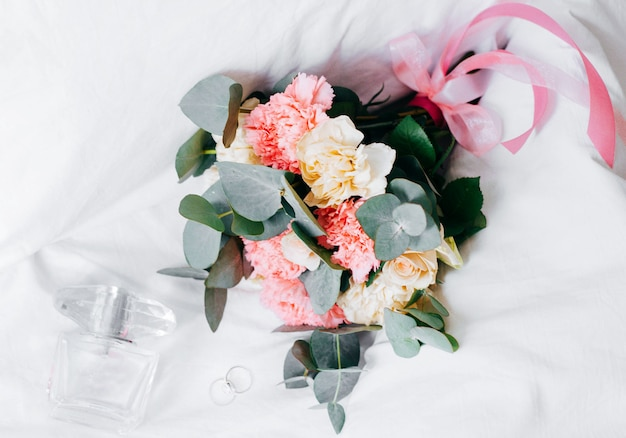 Perfume, rings and a beautiful bridal bouquet on the bed