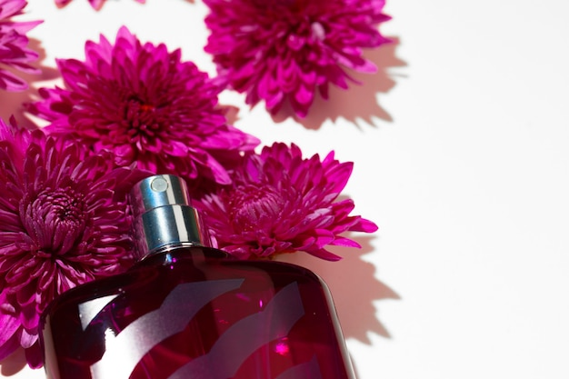 Perfume spray bottle and little flowers on gray background close up