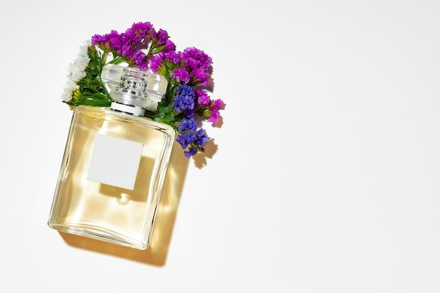 Perfume spray bottle and little flowers on gray background