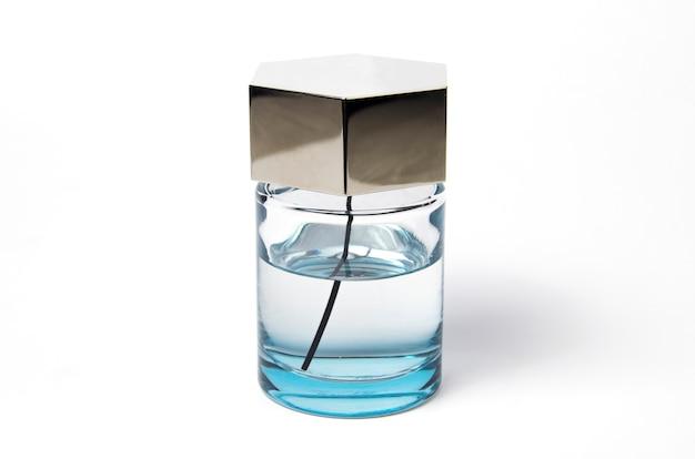白い背景の上の香水。青い液体のガラス瓶。