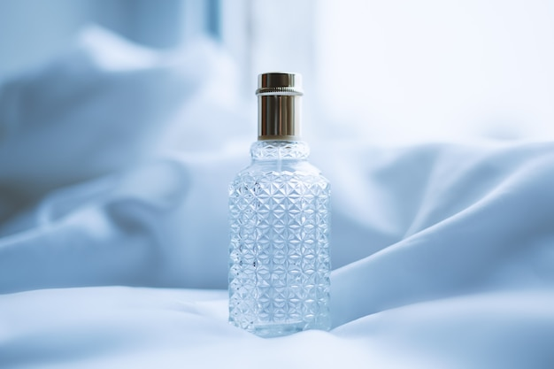 Perfume and white fabric in waves