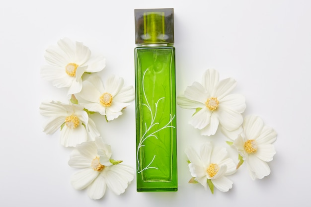 Perfume for women in green bottle and flowers around isolated on white. pleasant aromat or odor. floral fragrance