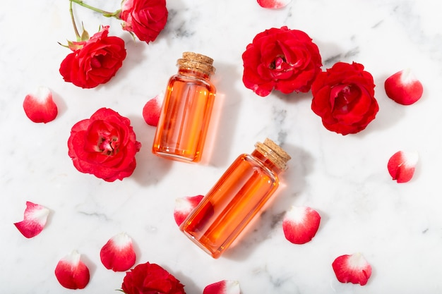 Perfumed rose water in glass bottle and small red roses with petals.