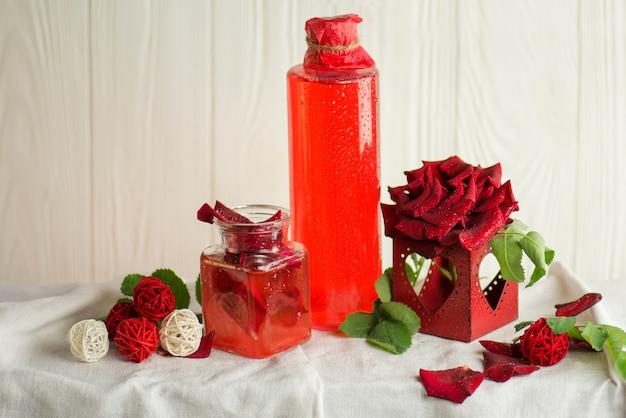 香りのよいローズウォーター。バラの花びらオイルをセットしたスパ。ピンクのバラの花とローズウォーターのグラス。新鮮な有機ローズウォーター