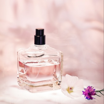 Perfumery in a bottle with a spray bottle on pink